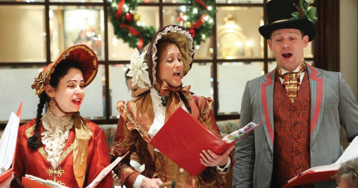 Three people singing Christmas Carols outside of the shops
