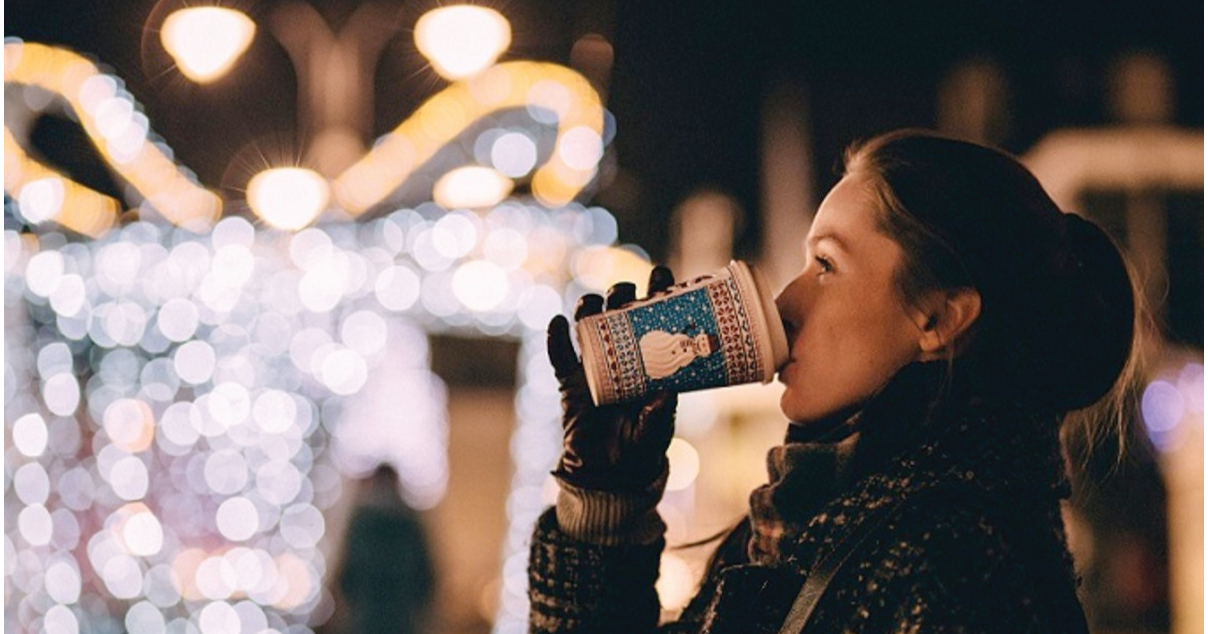 A woman drinking cocoa looking at Twinkle lights