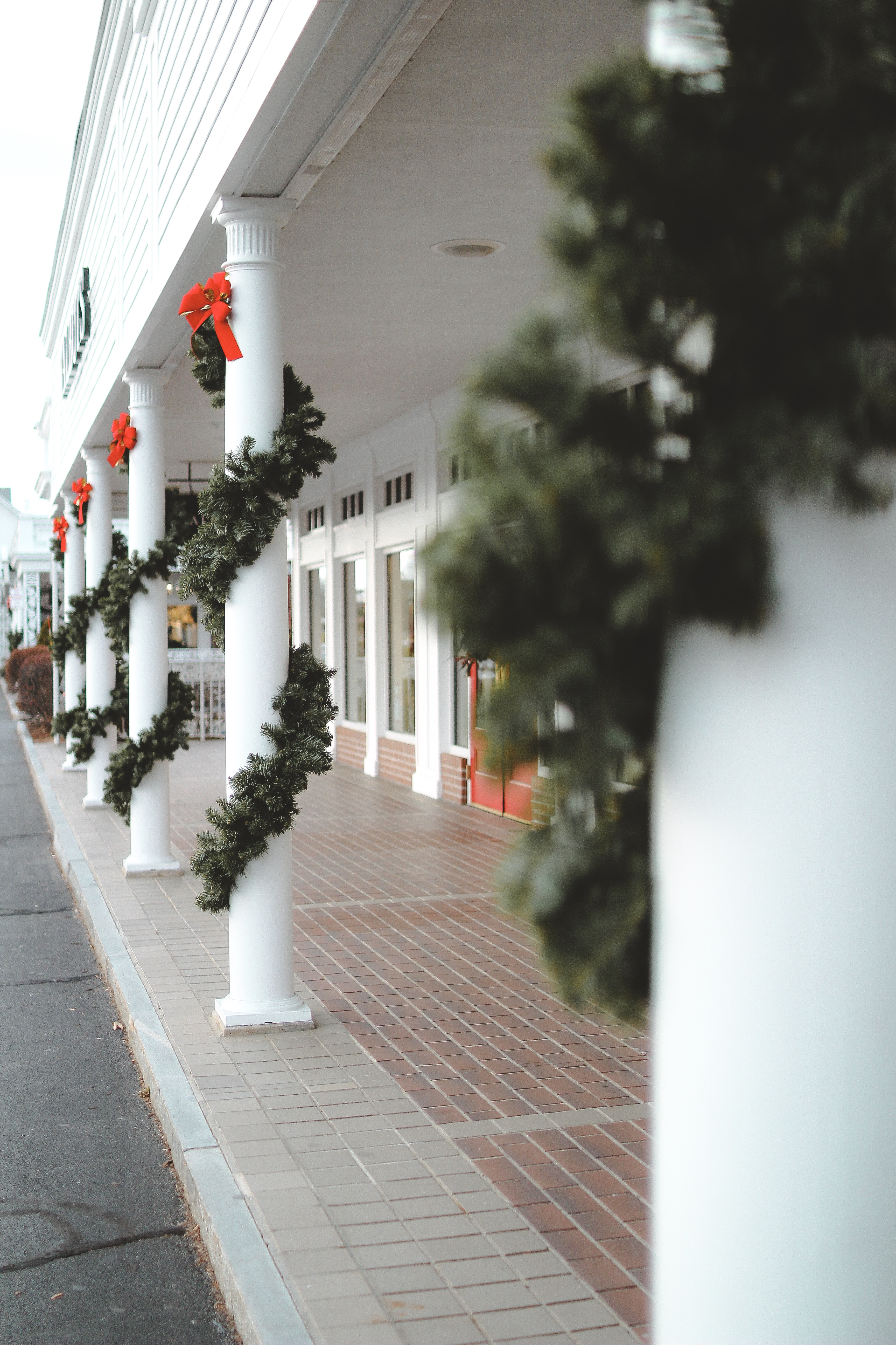 The Longmeadow shops decorated for Christmas with wreaths wrapped around poles.